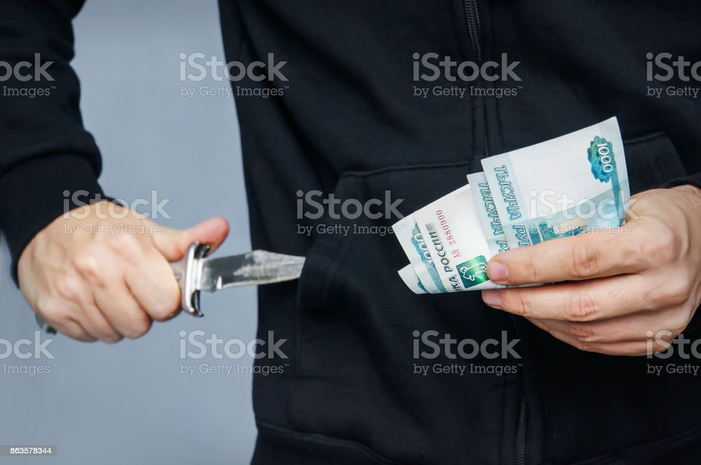Robber with knife in hand and Russian money stock photo