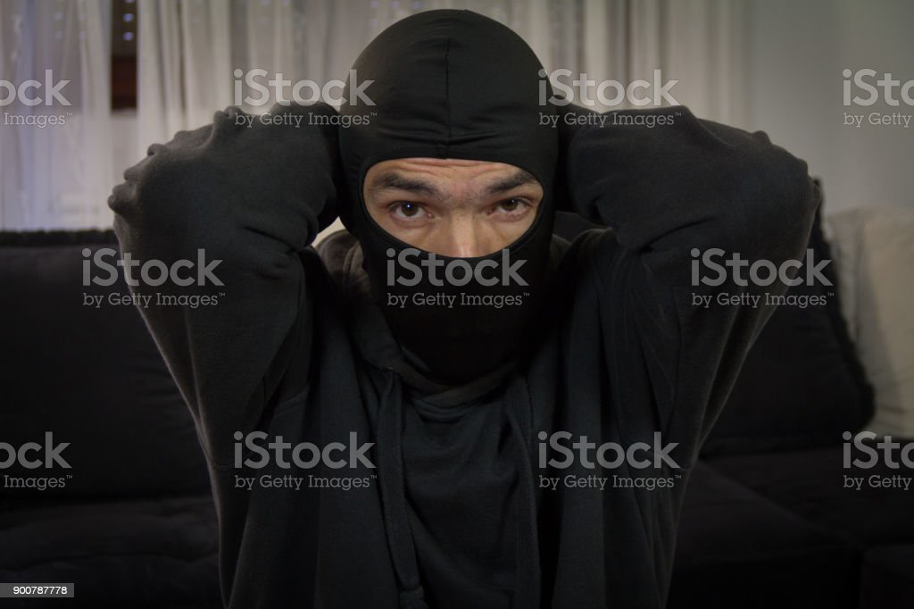 Robber with mask.  With handcuffs over his head stock photo