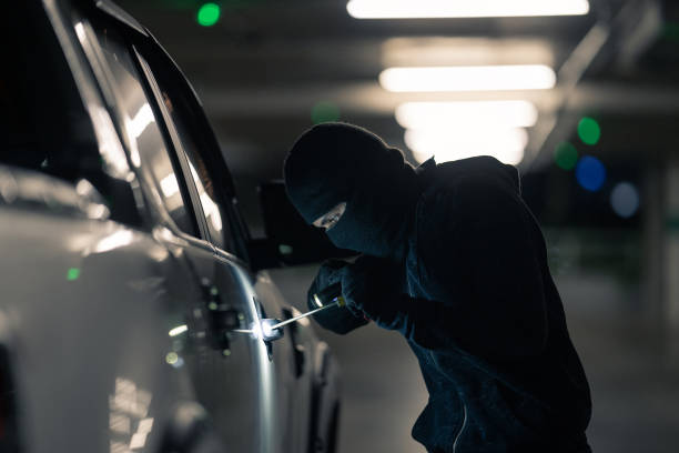 Robbers are robbing cars. Parked in the night parking stock photo
