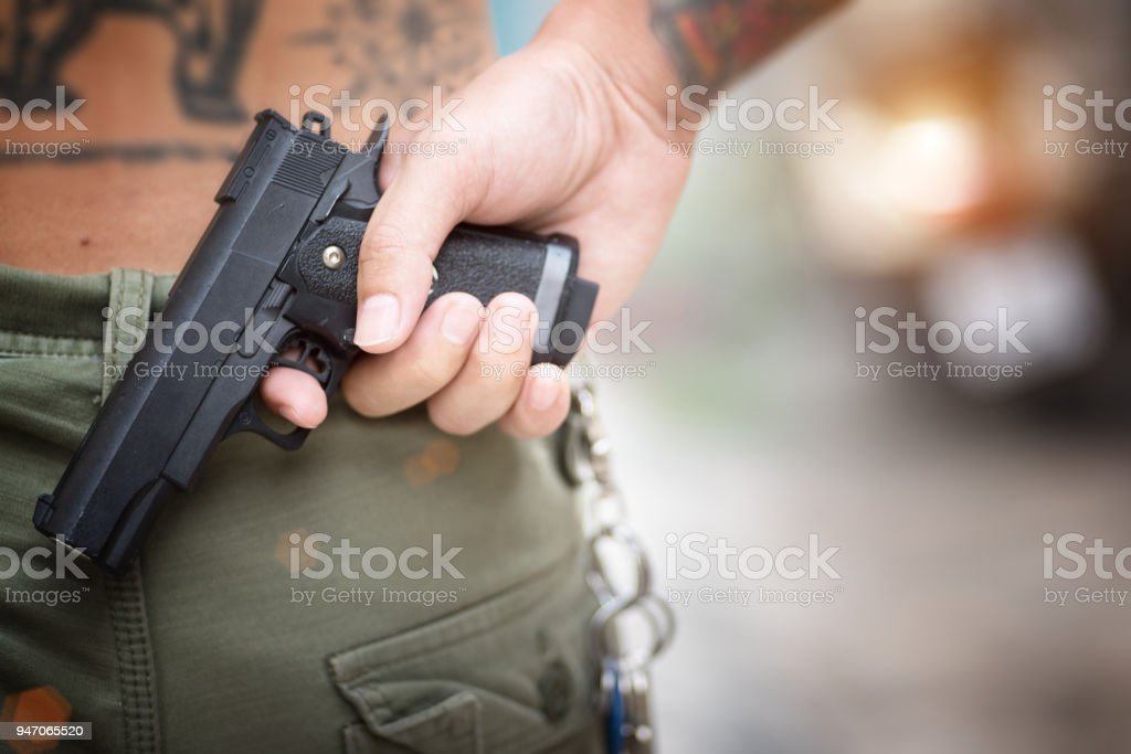 Robbers holding a gun at abandoned building. criminality concept. stock photo