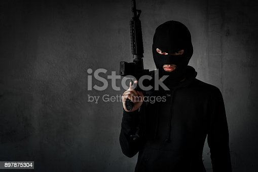 istock Robber,thieve or terrorist with gun and masked for  attack with assault rifle black suit ready shooting,aimming on copy space background violance concept 897875304