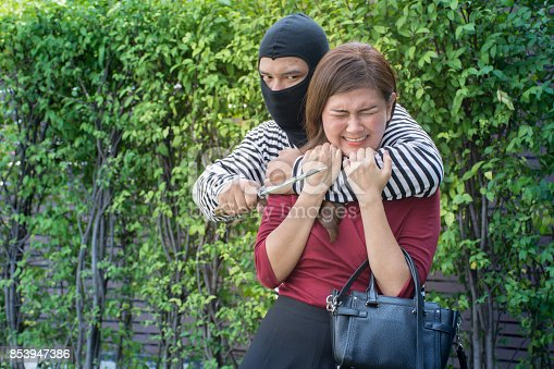istock Robbery make a scared young Asian victim to walk alone in a lonely alley/Hostage of terrorist or burglar threatening with knife 853947386