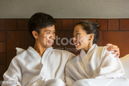 Attractive young Asian couple wearing bathrobes in bed