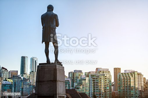Vancouver, British Columbia - January 7, 2019: Robert Burns Memorial monument in Stanley Park Vancouver overlooking Coal Harbor and the downtown city center with Vancouver Rowing Club in the foreground. The Robert Burns Memorial is an outdoor memorial and statue of Scottish poet Robert Burns, located in Stanley Park in Vancouver, British Columbia, Canada. It was dedicated on 25 August 1928, becoming the first statue erected in Vancouver. The creator of the statue is unknown.