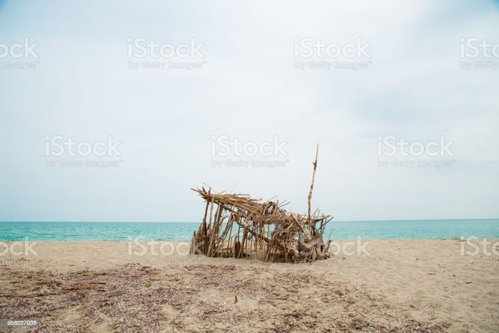 robinson crusoe refugee handmade shelter by the sea in abandoned shore of isolated island stock photo