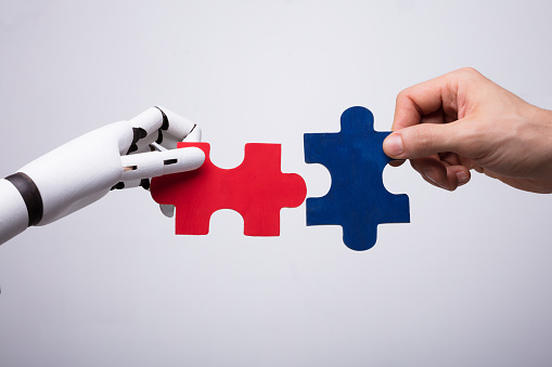 istock Robot And Human Hand Holding Jigsaw Puzzle 949212044