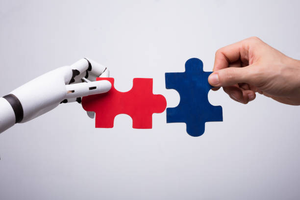 robot and human hand holding jigsaw puzzle - automatico foto e immagini stock