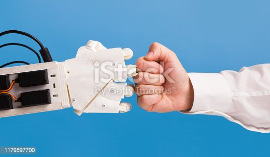 1050855372 istock photo Robot and human hand making fist bump gesture 1179597700