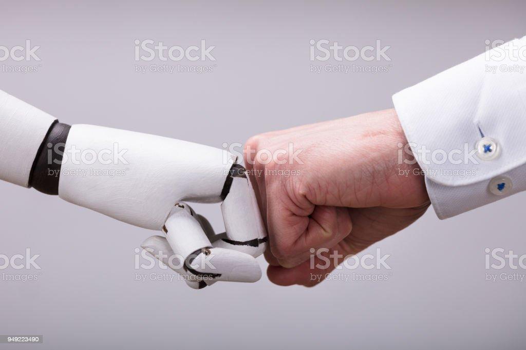 Robô e mão humana fazendo Fist Bump foto de stock royalty-free