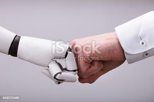 1050855372 istock photo Robot And Human Hand Making Fist Bump 949223490