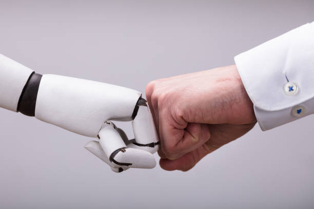 robot and human hand making fist bump - futuristic stock pictures, royalty-free photos & images