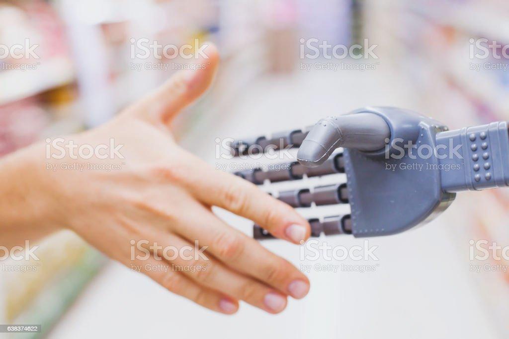 robot and human hands in handshake, high tech stock photo