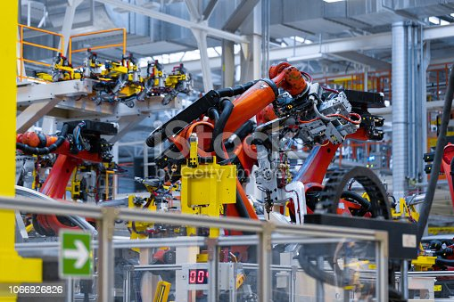 160554760istockphoto robot arm holds the detail of car. Car manufacturing plant 1066926826