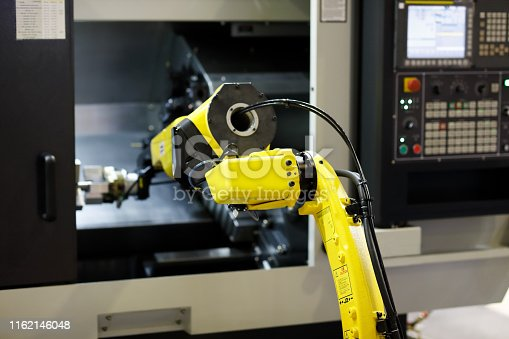 istock robot arm is loading detail into CNC lathe machine 1162146048