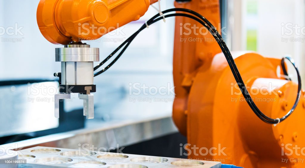 Robot arm working in a factory stock photo