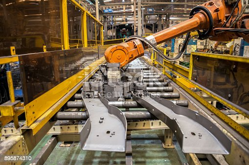 istock Robot arms handle tool keep automotive part to spot machine in car factory 895874310
