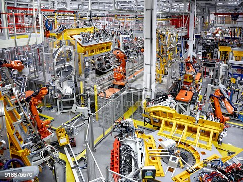 istock Robot arms in a car manufacturing factory 916875570