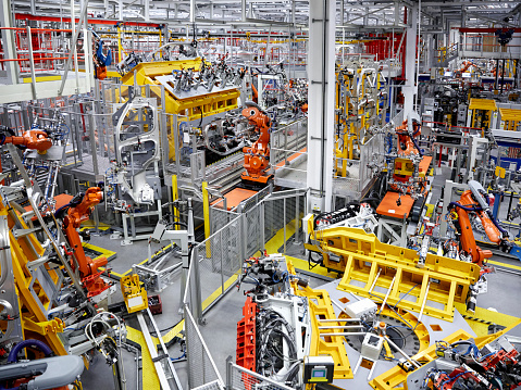 High angle view of robot arms in a car factory. Interior of automobile industry. Car production.