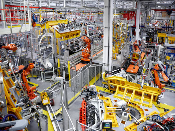 robot arms in a car manufacturing factory - robotics manufacturing stock photos and pictures