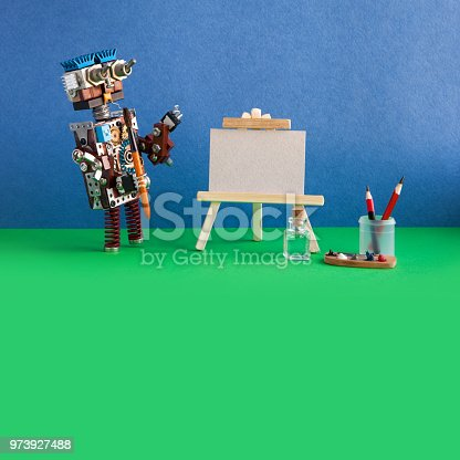 istock Robot artist begins to paint artwork. Creative robotic character with a watercolor brush, palette, wooden easel. Blue wall, green floor background. Copy space. Art studio advertising poster 973927488