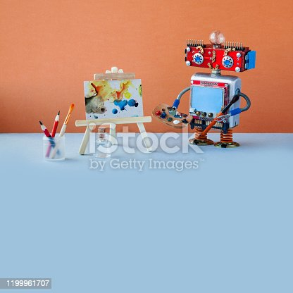 910163152 istock photo Robot artist paints an abstract picture with watercolors. Wooden easel and artist's tools palette, pencils case. Advertising poster studio school of visual arts interior. copy space 1199961707