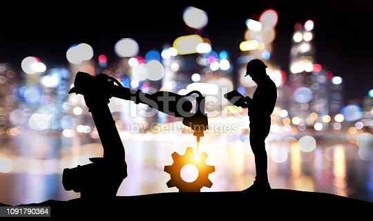 istock Robot assistant technology , industry 4.0 , artificial intelligence trend concept. Silhouette of engineer man control to automation robo advisor arm. Bokeh flare light effect with building background. 1091790364