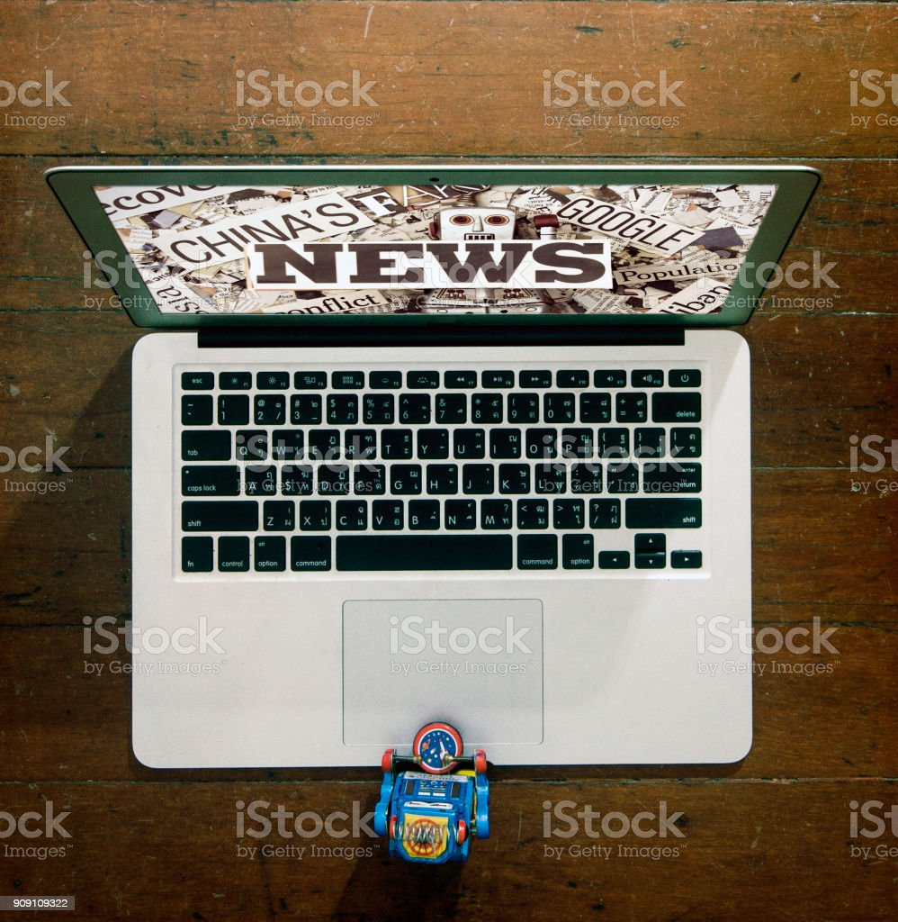robot at a laptop with  fake news stock photo