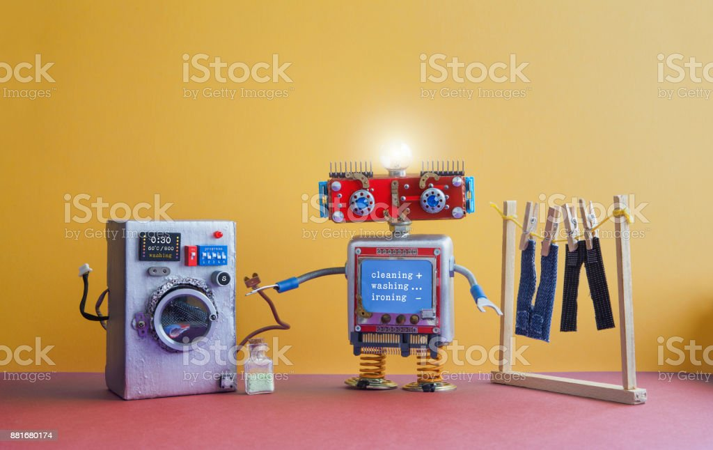 Robot automation laundry room. Robotic washer with message Cleaning, washing, ironing. Silver washing machine, men's jeans pants dried on clothesline with clothespins. yellow wall interior, red floor. Funny toys creative design stock photo