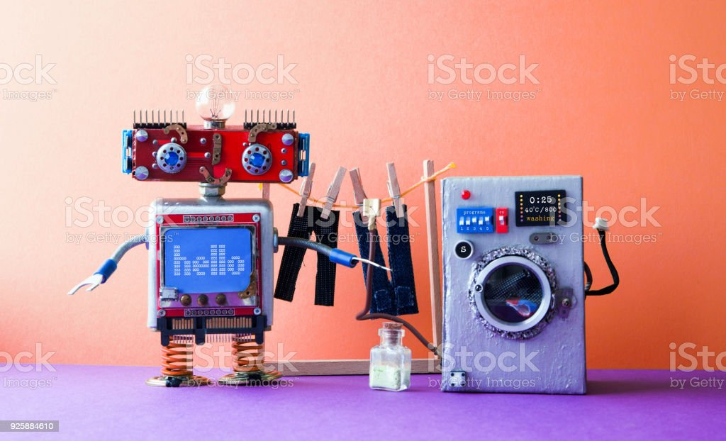 Robot automation laundry room. Robotic washer with message Hello. Silver washing machine, men's jeans pants dried on clothesline with clothespins. pink violet interior stock photo