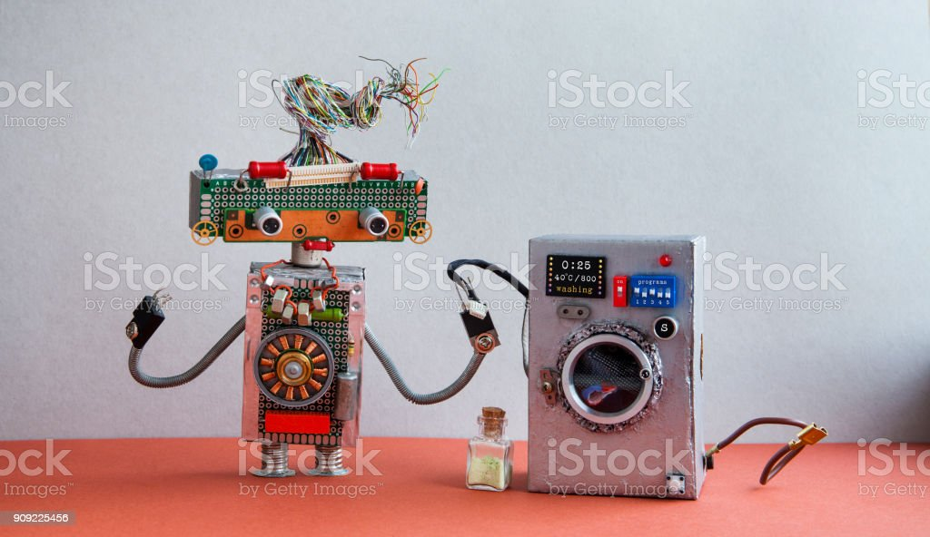 Robot automation laundry room. Silver washing machine, gray wall interior, red floor. Funny toys creative design stock photo