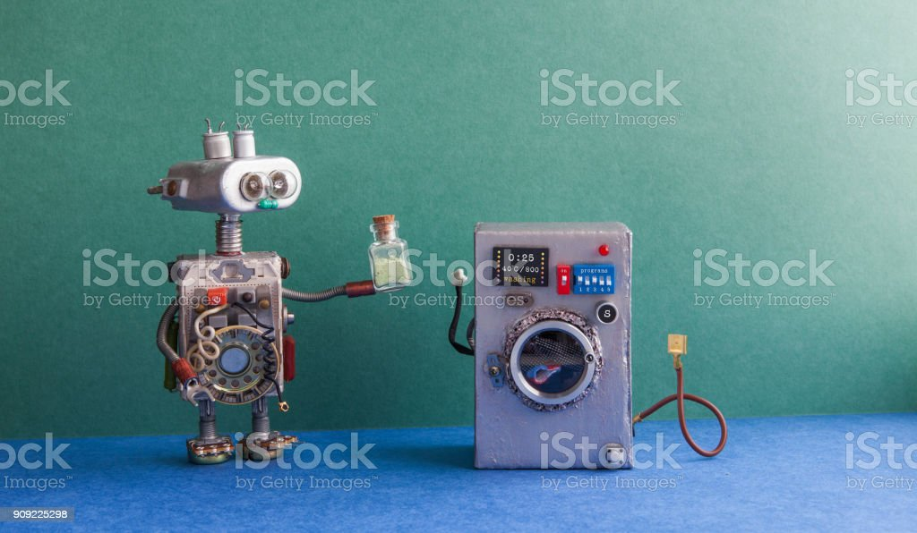 Robot automation laundry room. Silver washing machine, green wall interior, blue floor. Funny toys creative design stock photo