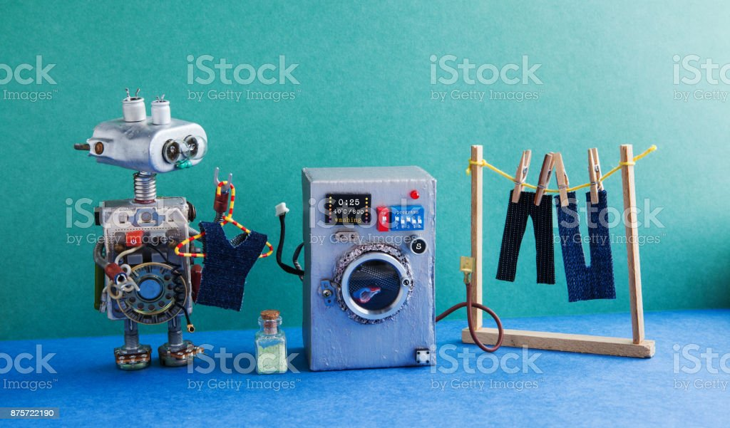 Robot automation laundry room. Silver washing machine, men's jeans pants dried on clothesline with clothespins. Green wall interior, blue floor. Funny toys creative design stock photo