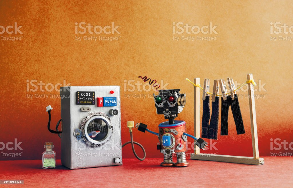 Robot automation laundry room. Silver washing machine, men's jeans pants dried on clothesline with clothespins. Aged golden orange wall interior, red floor. Funny toys creative design stock photo
