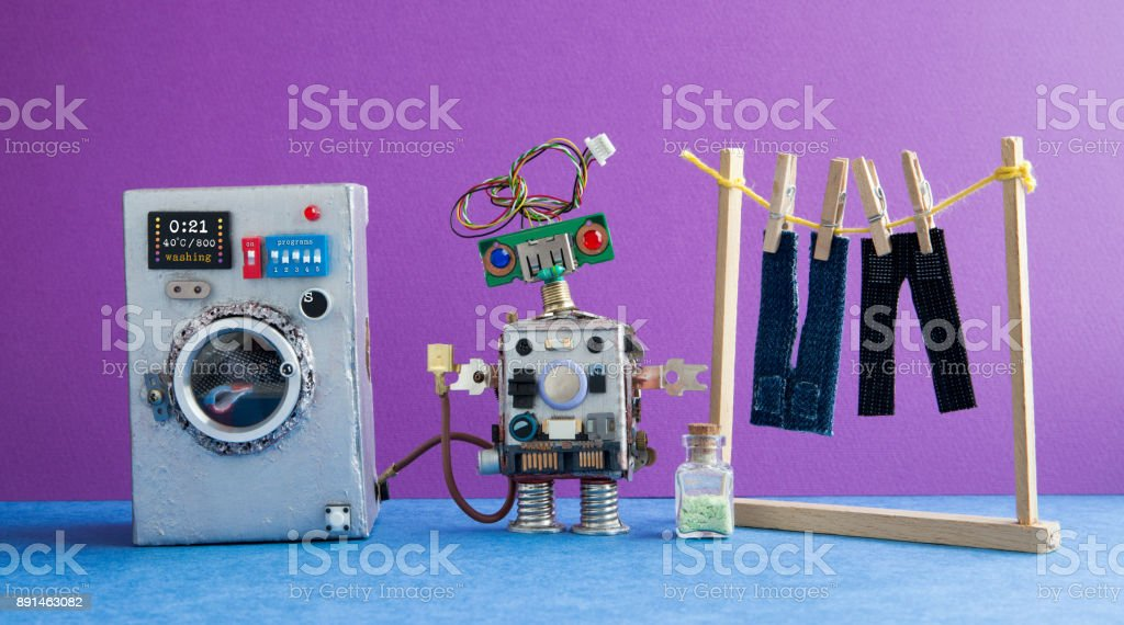 Robot automation laundry room. Silver washing machine, men's jeans pants dried on clothesline with clothespins. Violet wall interior, blue floor. Funny toys creative design stock photo