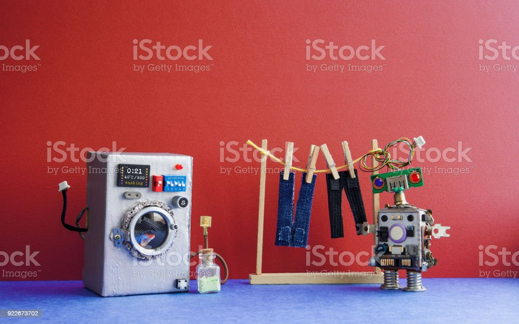 Robot automation laundry room. Silver washing machine, men's jeans pants dried on clothesline with clothespins. Red wall interior, blue floor. Funny toys creative design stock photo