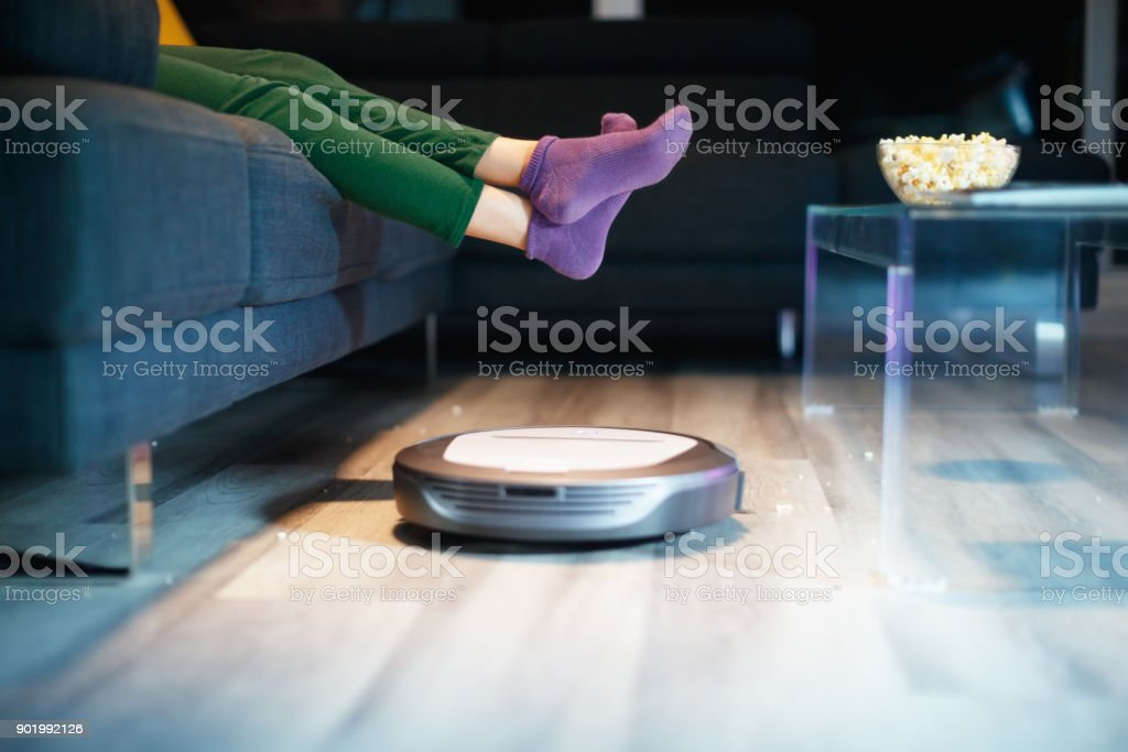Robot Cleaning Floor While Child Watches TV Movie stock photo