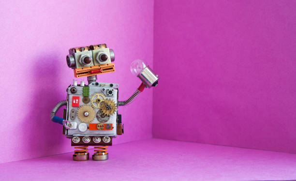 robot electrician holds a light bulb in his hand. creative design futuric robotic toy on pink background. copy space - industrial revolution stock pictures, royalty-free photos & images