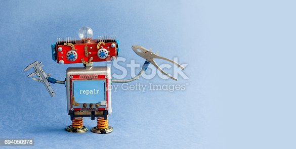 istock Robot engineer with calipers pliers. Creative handyman toy, mechanic cyborg worker on blue background. Industry 4.0 concept. Copy space 694050978