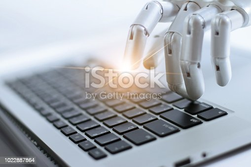 istock Robot finger point and working to laptop keyboard button, AI, Artificial Intelligence, Robotic hand on digital gray background. Futuristic technology concept. 1022887864
