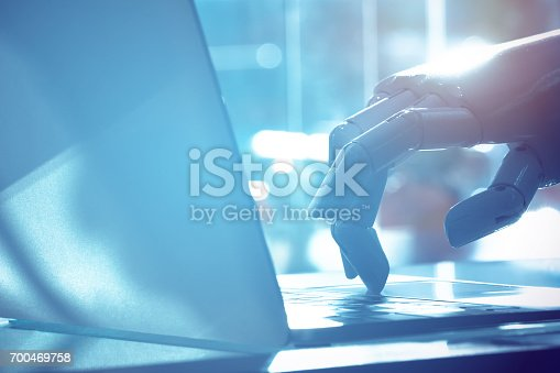 istock Robot finger point to laptop button with blue tone image. Chat bot , artificial intelligence , robo advisor , robotic concept. 700469758