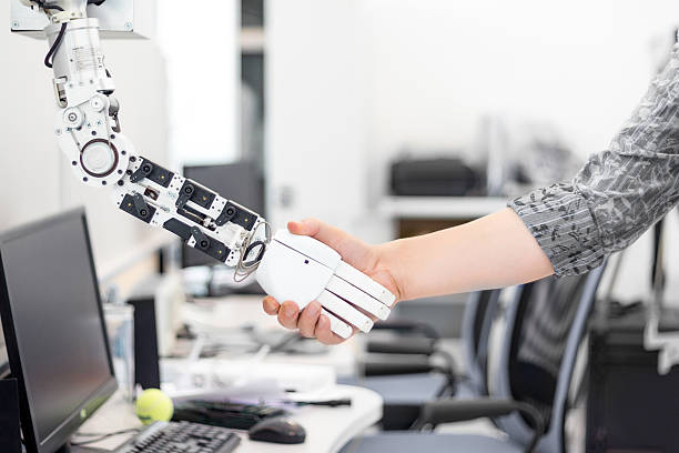 robot hand holds the objects drawn to a man's hand ストックフォト