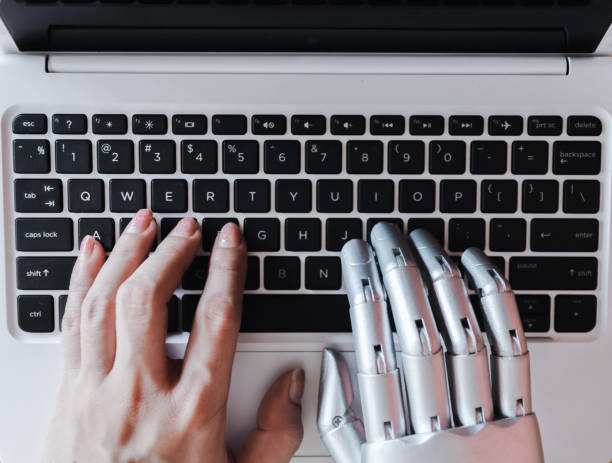 Robot hands and fingers point to laptop button advisor chatbot robotic artificial intelligence concept stock photo