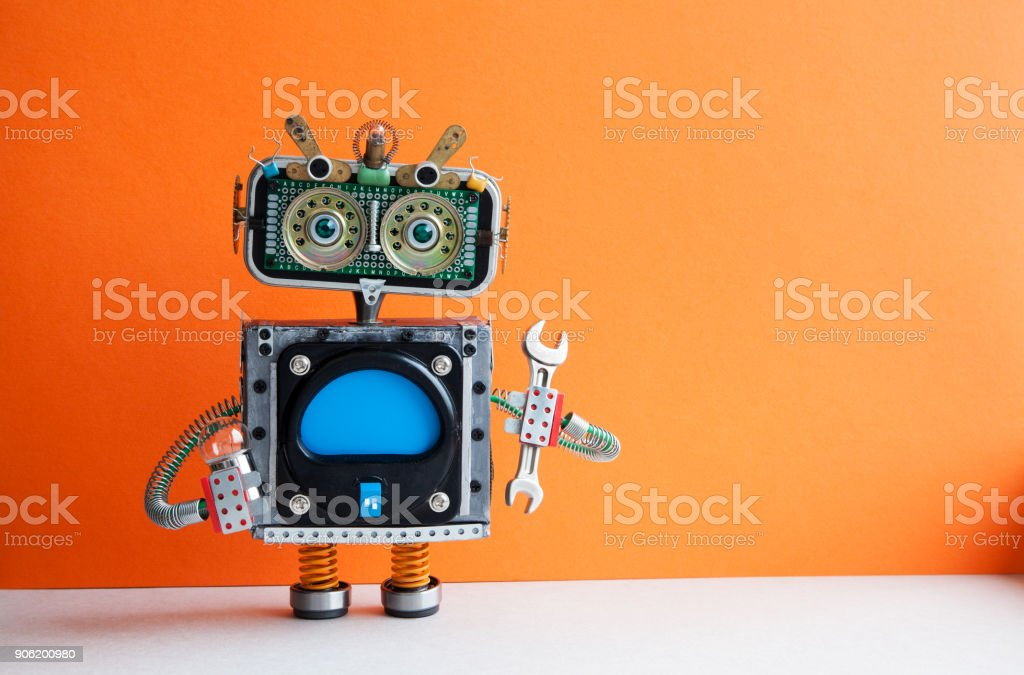 Robot handyman with hand wrench light bulb. Fixing maintenance concept. Creative design mechanic toy character. Orange wall, light floor background. Copy space stock photo