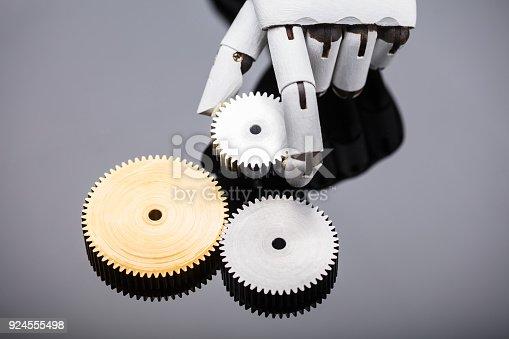 istock Robot Holding Metal Gear 924555498