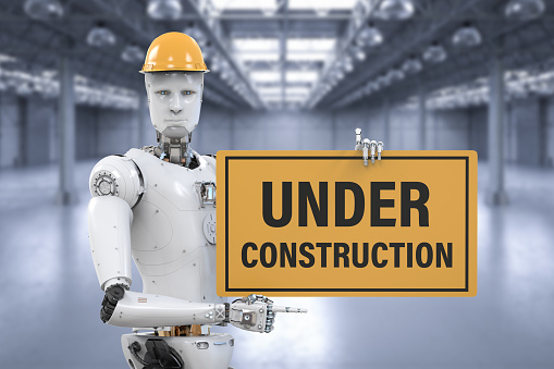 Robot Holding Under Construction Sign Stock Photo - Download Image Now