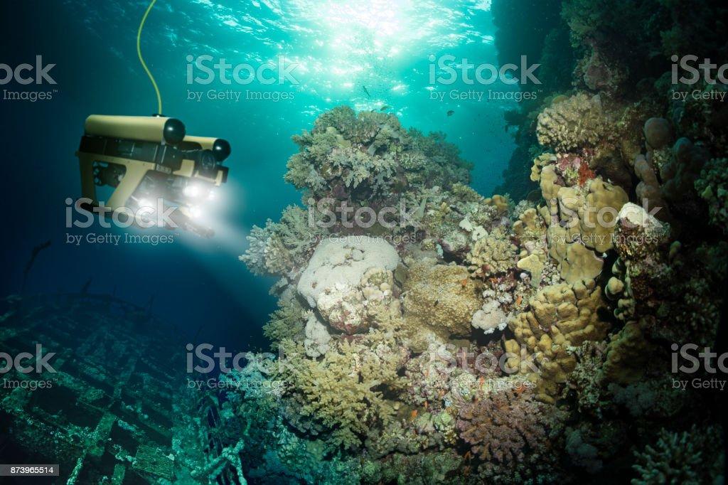 Robot inspects a sunken ship deep under water stock photo