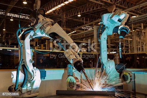 989526318 istock photo robot is welding in car factory 672453804
