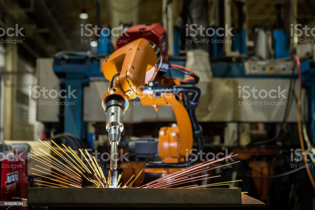 Robot is welding metal part in automotive industrial stock photo