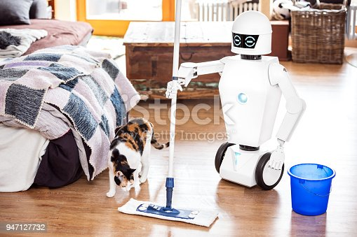 istock robot or automatic floor scrubber is cleaning the floor of a living room, while a cat is coming. 947127732