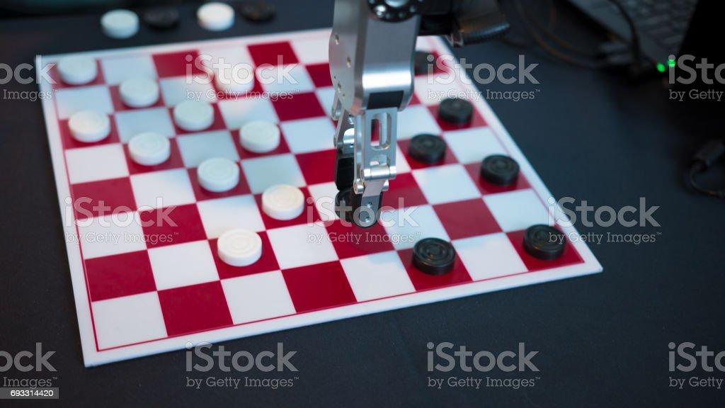 Robot jugando damas. Manipulador de la mano mueve damas. foto de stock libre de derechos